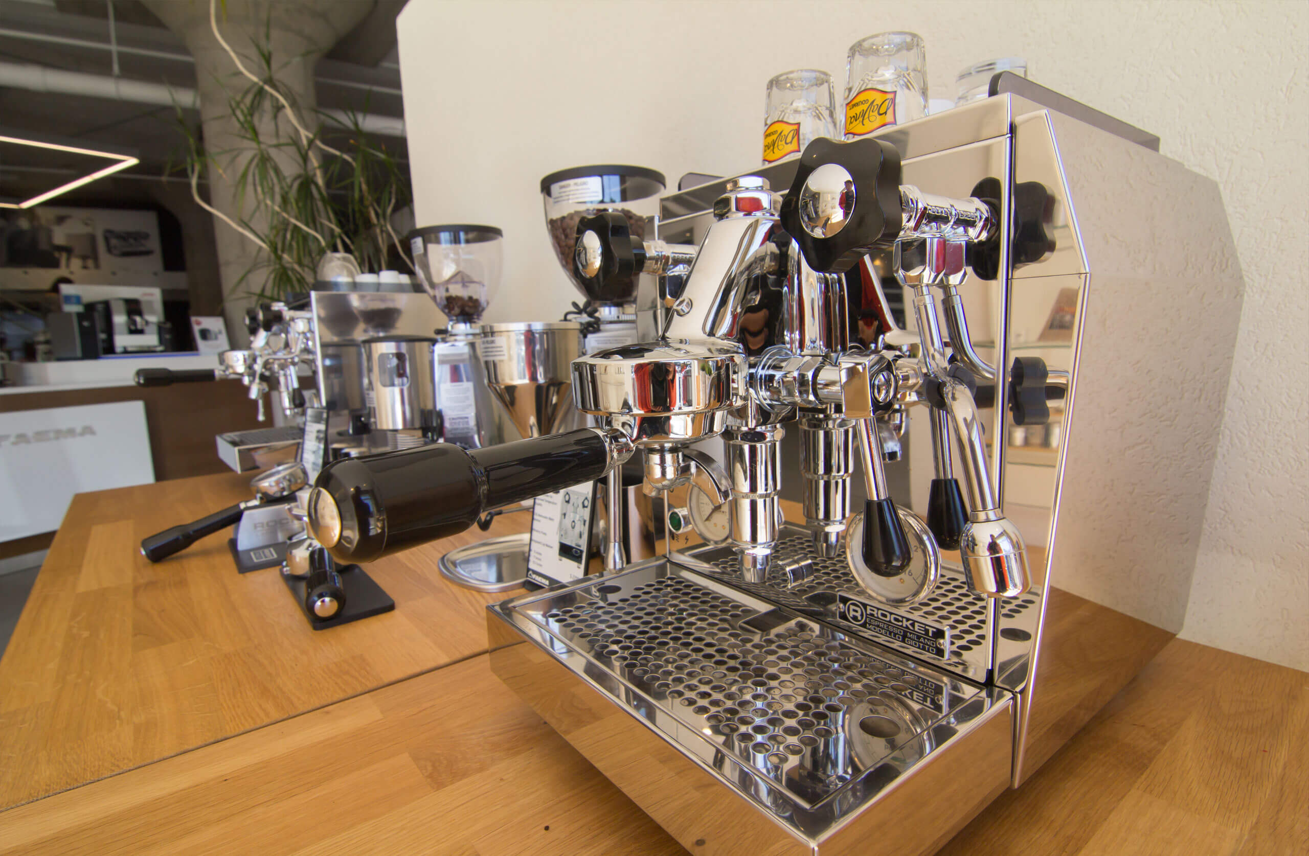 Cappuccino and espresso machines are lined on the counter top.